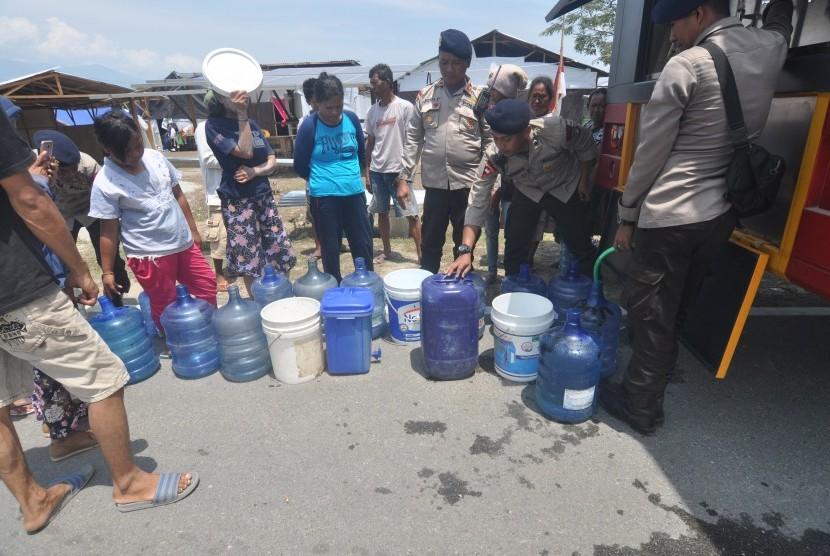Pengungsi korban gempa dan pencairan tanah (likuifaksi) mengambil air bersih dan air siap minum pada kendaraan Water Treatmen milik Polri dilokasi pengungsian di Petobo, Palu, Sulawesi Tengah, Selasa (16/10/2018).
