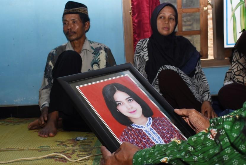 Seorang kerabat memegangi foto salah seorang pramugari pesawat Lion Air JT 610 yang mengalami kecelakaan, Alfiani Hidayatul Solikah di depan kedua orangtua Alfiani, Slamet (kiri) dan Kartini (kedua kiri) di rumahnya Desa Mojorejo, Kebonsari, Kabupaten Madiun, Jawa Timur, Selasa (30/10/2018).