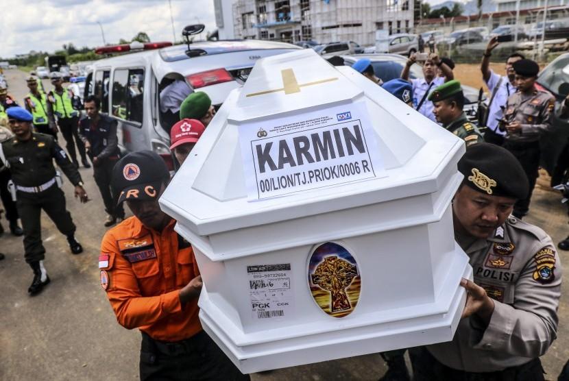 Personel Basarnas dibantu TNI dan Polri memanggul peti jenazah korban jatuhnya pesawat Lion Air JT 610, Karmin, setibanya di terminal cargo Bandara Depati Amir, Pangkalpinang, Kepulauan Bangka Belitung, Jumat (5/11/2018).