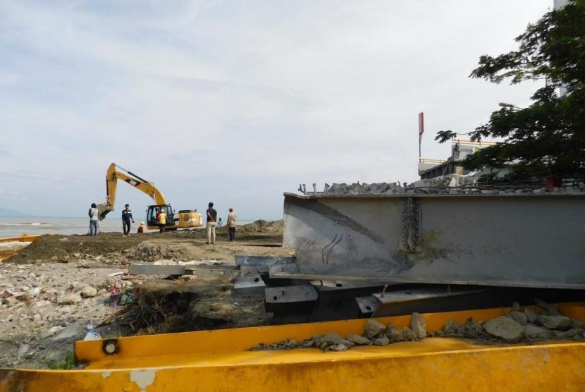 Petugas menggunakan alat berat  untuk meratakan sisa reruntuhan puing Jembatan Palu IV atau Jembatan Ponulele, Palu, Sulawesi Tengah paska gempa dan tsunami, Kamis (8/11).