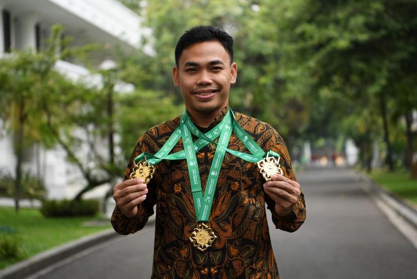 Lifter Eko Yuli Irawan memperlihatkan medali seusai diterima oleh Presiden Joko Widodo di Kompleks Istana Kepresidenan, Jakarta, Kamis (8/11/2018).