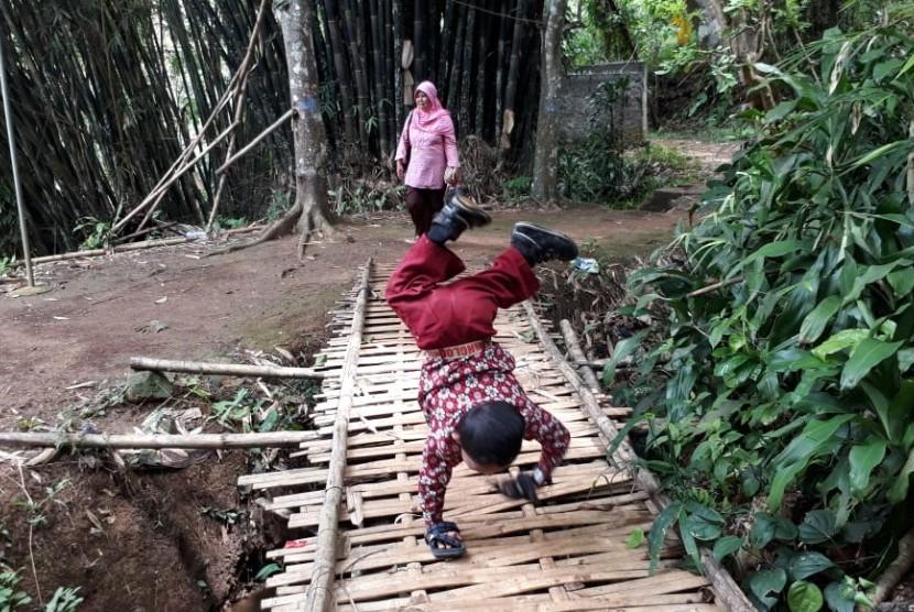 Pelajar Kelas III SDN 10 Cibadak Kabupaten Sukabumi Mukhlis Abdul Kholik (8) berangkat ke sekolah dengan merangkak sejauh tiga kilometer karena kelainan pada bagian kakinya Kamis (8/11).