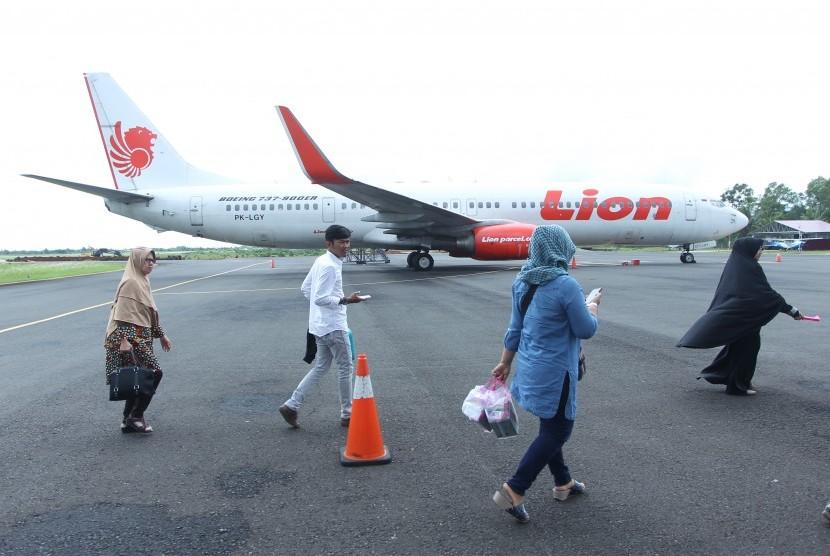 Penumpang berjalan di samping pesawat Lion Air jenis Boeing 737-900 ER, registrasi PK-LGY dengan nomor penerbangan JT633 yang terparkir setelah di