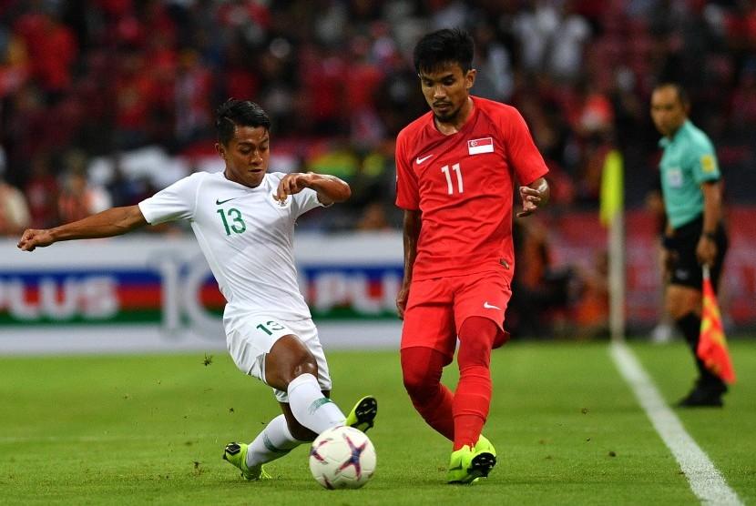 Pemain timnas Indonesia Febri Hariyadi (kiri) mencoba merebut bola dari pemain timnas Singapura Muhammad Yasir Hanapi dalam penyisihan grub B Piala AFF 2018 di Stadion Nasional Singapura, Jumat (9/11/2018).