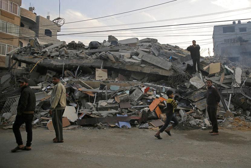 Warga melintasi bangunan yang hancur akibat serangan Israel ke Kota Gaza, Rabu (14/11).