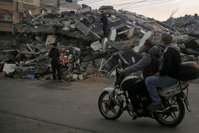 Warga melintasi bangunan yang hancur akibat serangan Israel ke Kota Gaza, Rabu (12/11).