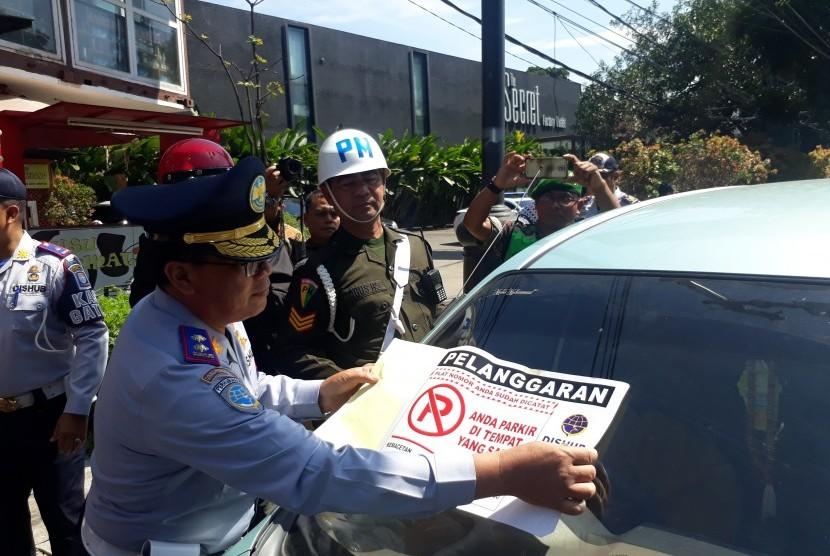 Petugas menindak kendaraan yang diparkir sembarangan di Jalan Riau, Kota Bandung.