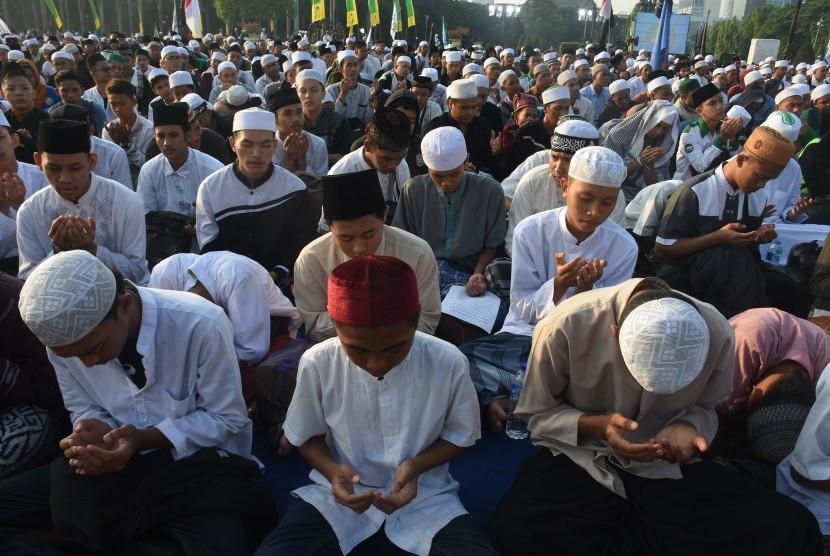 Ribuan umat muslim berdoa saat menghadiri Tabligh Akbar Majelis Rasulullah dalam peringatan Maulid Muhammad SAW 1440 H di Lapangan Monas, Jakarta, Selasa (20/11).