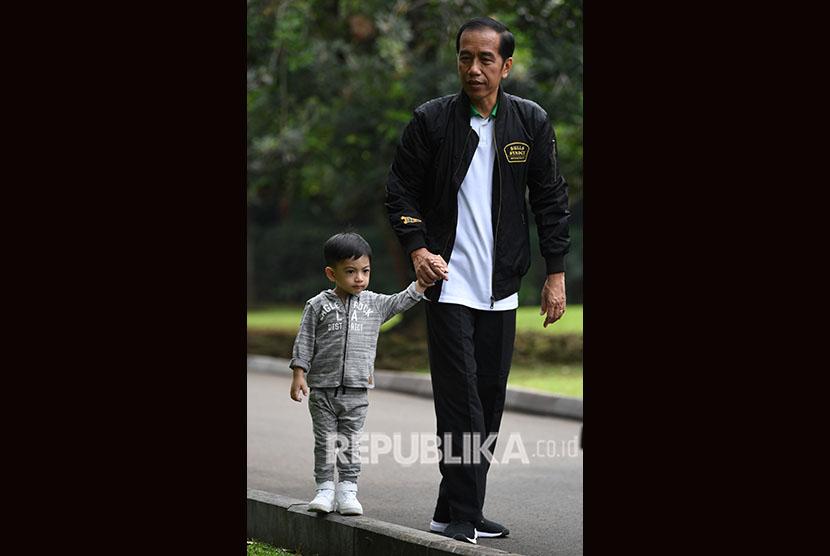 Presiden Joko Widodo menggandeng cucu Jan Ethes di Istana Bogor, Jawa Barat, Sabtu (8/12).