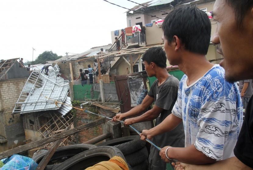 Sejumlah warga bergotong-royong mengevakuasi sisa bangunan rumah terdampak bencana angin puting beliung / Ilustrasi