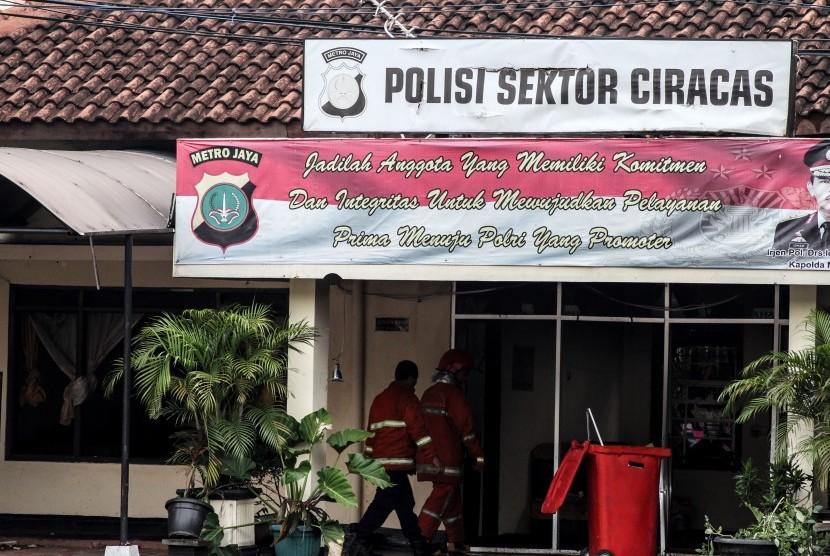 Petugas pemadam kebakaran bergegas seusai memadamkan api yang melanda Polsek Ciracas, Jakarta, Rabu (12/12/2018).