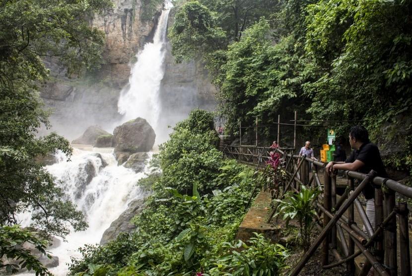 Pengunjung menikmati keindahan air terjun di kawasan wisata alam Geopark Curug Cimarinjung, Ciemas, Kabupaten Sukabumi, Jawa Barat, Minggu (16/12/2018).