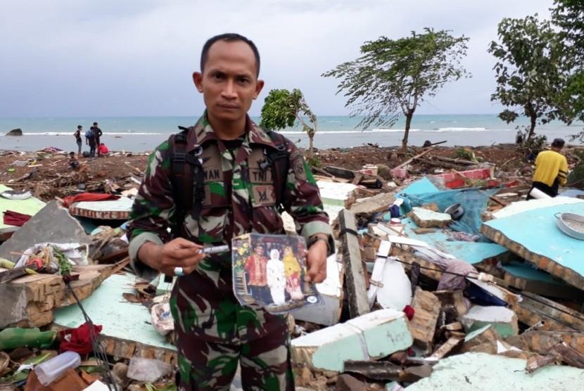 Seorang anggota TNI AL sedang menunjukkan foto-foto anggota keluarga Asep di reruntuhan rumahnya di Desa Way Muli, Rajabasa, Kabupaten Lampung Selatan.