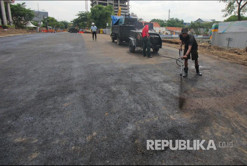 Pekerja melakukan proses 'prime coat' pada urukan tanah sebelum di aspal di lokasi jalan ambles di Jalan Raya Gubeng, Surabaya, Jawa Timur, Rabu (26/12/2018).