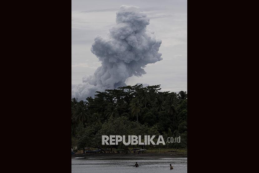 Warga beraktivitas dengan latar belakang erupsi Gunung Anak Krakatau di Pelabuhan Pulau Sebesi, Lampung Selatan, Lampung, Selasa (1/1/2019).