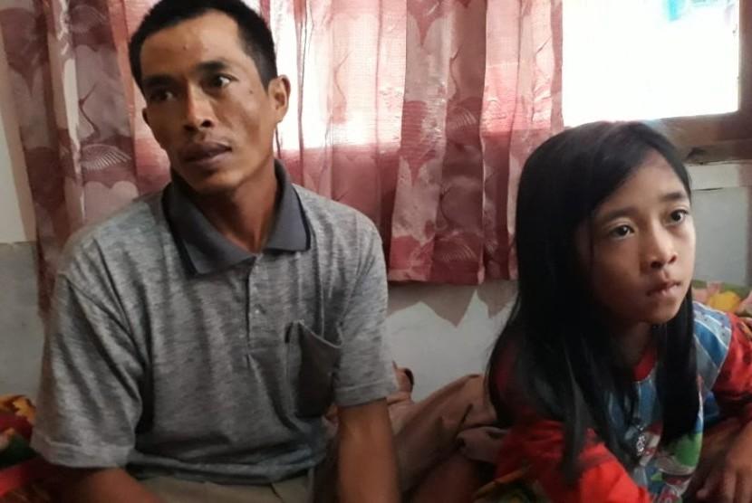 Seorang korban selamat akibat longsor di Desa Sirna Resmi Kecamatan Cisolok Kabupaten Sukabumi Tandi (32) dan anaknya Sindi (8) ditemui di rumah kerabatnya Rabu (2/1). Tandi kehilangan sebanyak 14 anggota keluarga.