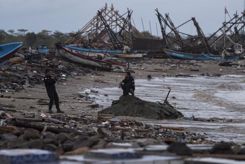 Warga memotret rekannya di antara puing-puing yang rusak karena tsunami Selat Sunda di Sumur, Pandeglang, Banten, Kamis (3/1/2019).