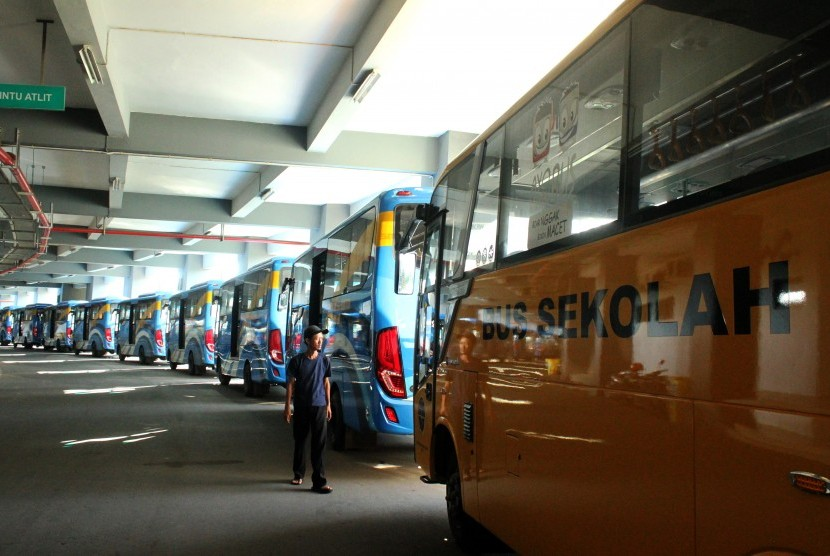 Warga melintas di samping deretan bus Trans Patriot yang terparkir, di Bekasi, Jawa Barat, Kamis (3/1/2019).