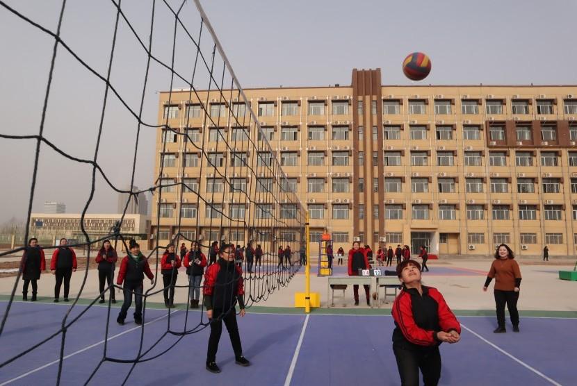 Para peserta didik kamp pendidikan vokasi etnis Uighur di Kota Kashgar, Daerah Otonomi Xinjiang, Cina, berolahraga di lapangan voli pelataran asrama, Jumat (3/1/2019).