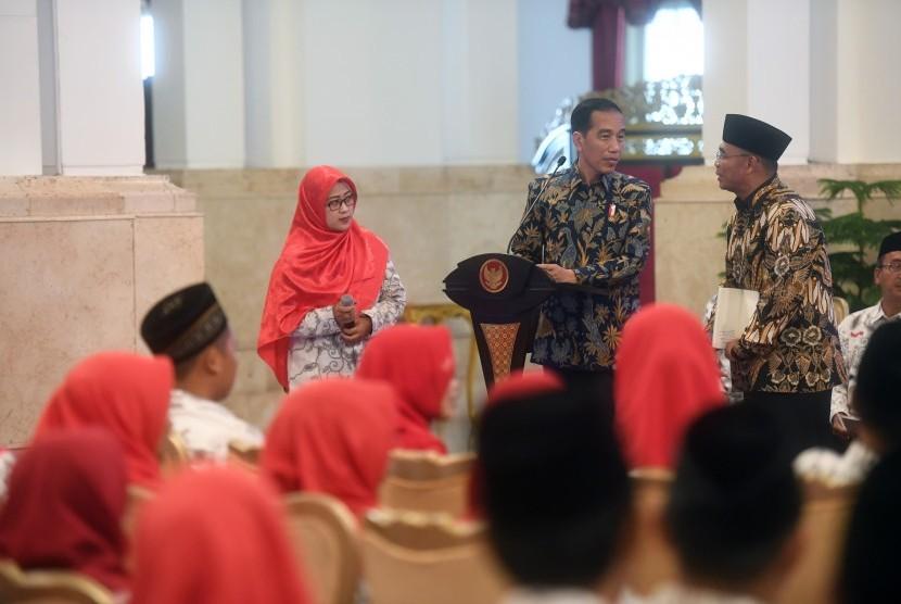 Presiden Joko Widodo (kanan) berdiskusi dengan Mendikbud Muhadjir Effendy (kanan) saat acara silaturahmi dengan Persatuan Guru Seluruh Indonesia (PGSI) di Istana Negara, Jakarta, Jumat (11/1/2019).