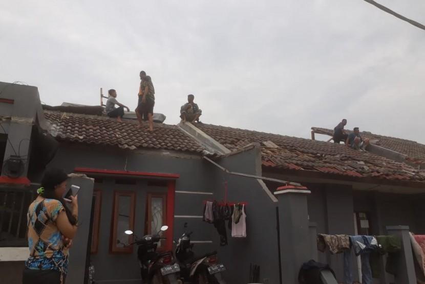Sejumlah warga dan relawan di Blok B 24, Perumahan Rancaekek Permai 2, Kecamatan Rancaekek, Kabupaten Bandung tengah membersihkan puing-puing bangunan rumah yang rusak akibat angin puting beliung, Jumat (11/1).