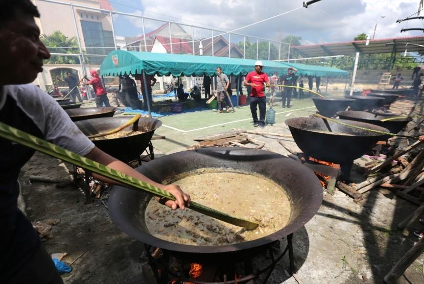 Warga secara gotong royong memasak kuah beulangong (kari daging sapi) pada perayaan maulid Nabi Muhammad SAW di Desa Ilie, Banda Aceh, Aceh, Ahad (13/1/2019).