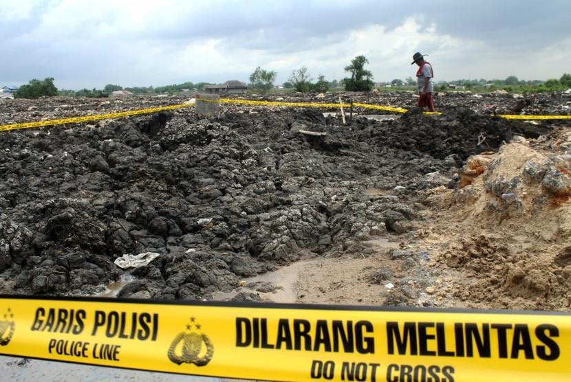 Warga melintas di dekat area lahan pembuangan pasir yang diduga mengandung limbah Bahan Beracun Berbahaya (B3), di kawasan Banjir Kanal Timur, Tarumajaya, Kabupaten Bekasi, Jawa Barat, Rabu (16/1/2019).