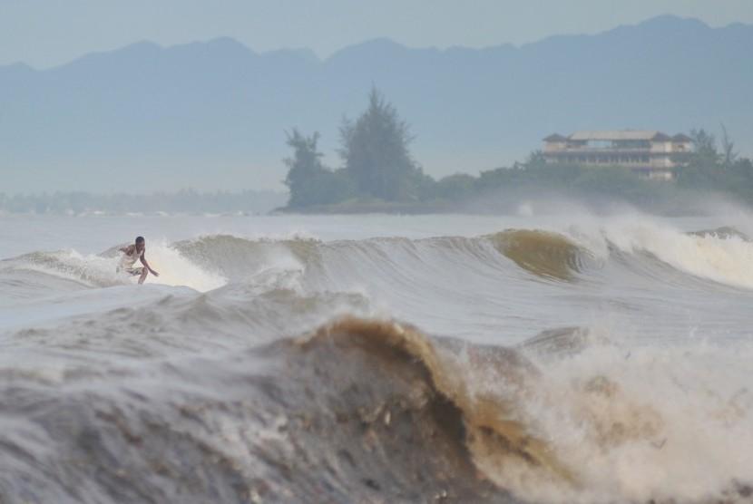 Peselancar memanfaatkan gelombang tinggi (ilustrasi)