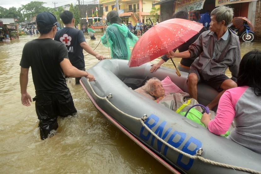 Tim relawan mengevakuasi warga korban banjir di Kelurahan Paccerakkang, Makassar, Sulawesi Selatan, Selasa (22/01/2019).