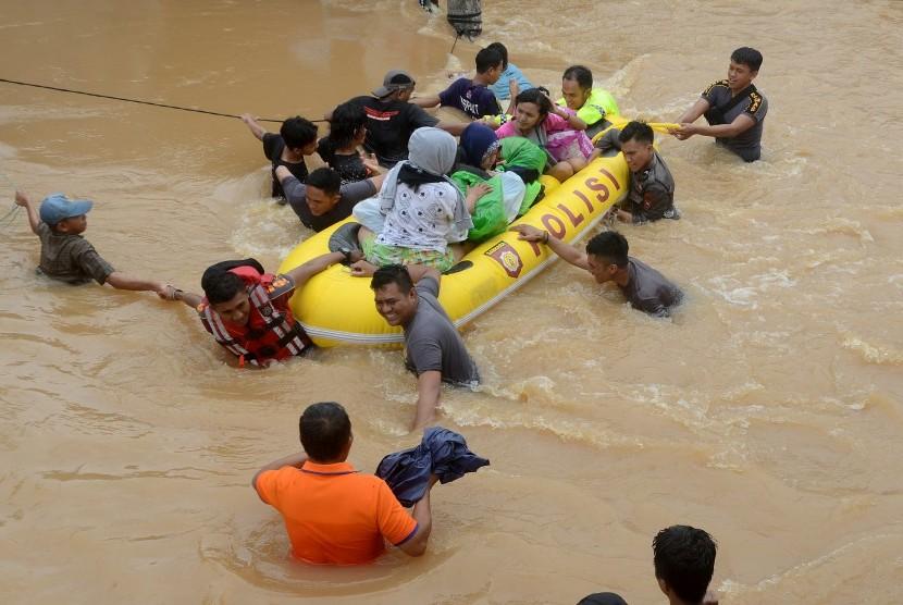 Tim relawan mengevakuasi warga yang terjebak banjir di Perumahan Bung Permai, Makassar, Sulawesi Selatan, Rabu (23/1/2019).