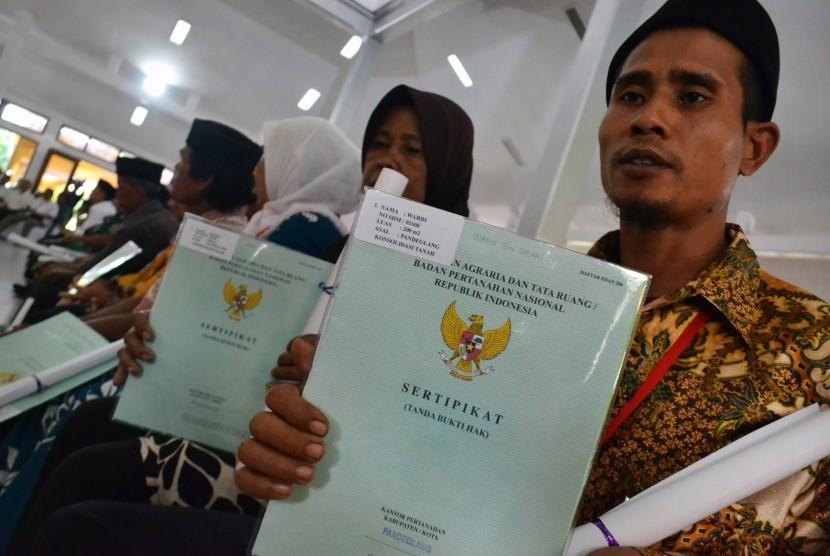 Warga menunjukan sertifikat tanah yang dibagikan pemerintah di Pendopo Bupati Pandeglang, di Pandeglang, Banten, Rabu (23/1/2019).