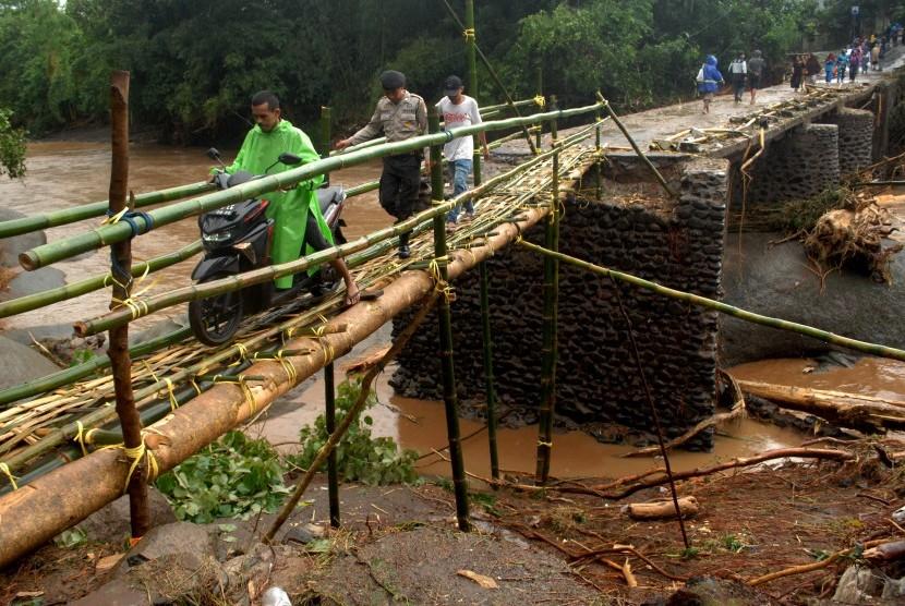 Warga melewati jembatan darurat sementara yang terbuat dari bambu di desa Pallatikang, Kabupaten Gowa, Sulawesi Selatan, Kamis (24/1/2019).