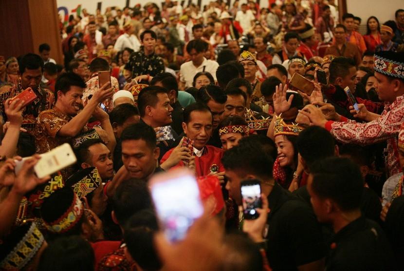 Capres nomor urut 01 Joko Widodo (tengah) berswafoto bersama Masyarakat adat Dayak usai hadiri silahturahmi nasional masyarakat Dayak di Jakarta, Sabtu (26/1/19).