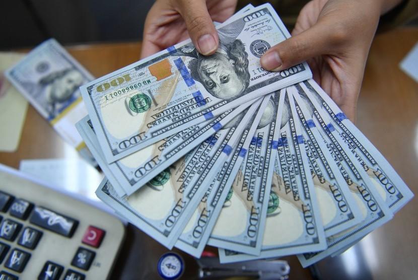 Karyawan menghitung mata uang dolar Amerika Serikat di gerai penukaran mata uang asing. ilustrasi