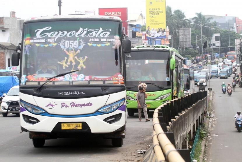 Sejumlah bus angkutan umum antarkota antarprovinsi (AKAP) berhenti menunggu penumpang di terminal bayangan jembatan layang Cibinong, Kabupaten Bogor, Jawa Barat, Senin (28/1/2019).