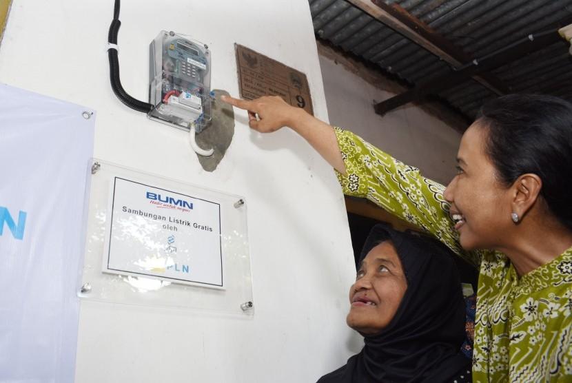 Menteri Badan Usaha Milik Negara (BUMN) Rini Soemarno (kanan) menyalakan lampu listrik saat meninjau rumah warga penerima bantuan sambungan listrik gratis untuk masyarakat tidak mampu melalui Program BUMN Hadir Untuk Negeri di Magetan, Jawa Timur, Jumat (1/2/2019).