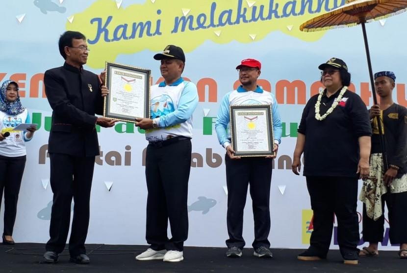 Bupati Indramayu Supendi (topi hitam) menerima penghargaan MURI yangdiserahkan oleh Senior Manager MURI Yusuf Ngadri dan disaksikan Menteri Lingkungan Hidup dan Kehutanan Republik Indonesia Siti Nurbaya Bakar pada acara Coastal Clean Up yang digeIar di Pantai Kejawanan Cirebon, Jumat (15/2).