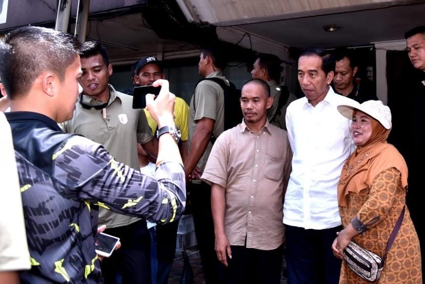 Calon presiden nomor urut 01, Jokowi, berfoto bersama warga usai menyantap hidangan makan siang bersama keluarganya di Kelapa Gading, Jakarta Utara, Ahad (17/2) siang.