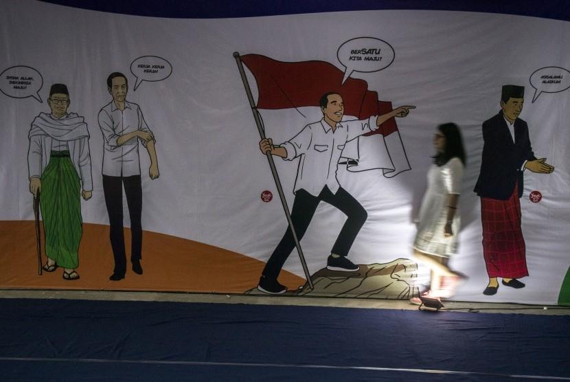 Relawan berpose di depan gambar Calon Presiden nomor urut 01 Joko Widodo jelang nonton bareng (nobar) debat Capres 2019 di Rumah Kerja Relawan 01 Jawa Barat, Bandung, Jawa Barat, Ahad (17/2/2019).