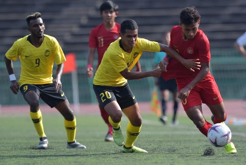 Timnas U-22 Indonesia lawan Malaysia: Pemain Timnas U-22 Indonesia Osvaldo Haay (kanan) berebut bola dengan pemain Malaysia Muhammad Nazirul Afif Ibrahim (tengah) dalam pertandingan Grup B Piala AFF U-22 di Stadion Nasional Olimpiade Phnom Penh, Kamboja, Rabu (20/2/2019).