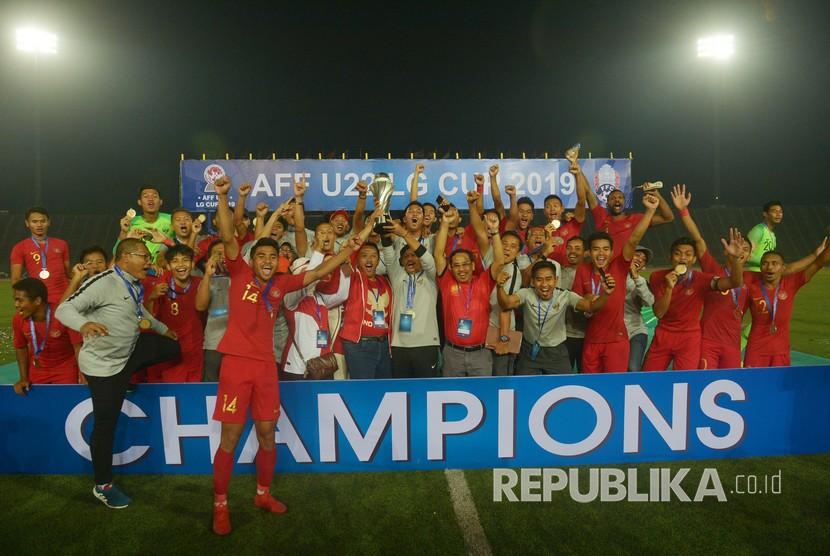 Pelatih Timnas U-22 Indra Sjafri (kedelapan kiri) bersama Menteri Pemuda dan Olah Raga Imam Nahrawi (ketujuh kiri) memegang piala beserta pemain dan Ofisial Timnas Indonesia seusai penganugerahan Piala AFF U-22 2019 di Stadion Nasional Olimpiade Phnom Penh, Kamboja, Selasa (26/2/2019).