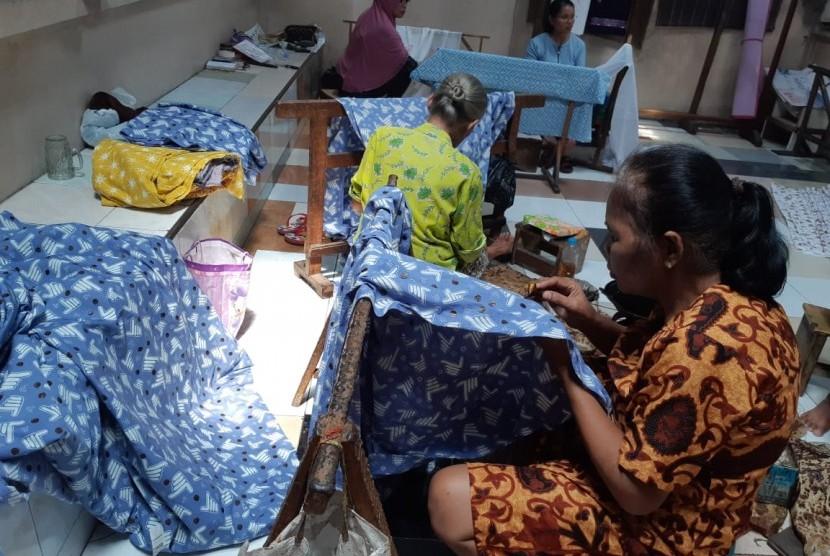 Perajin batik memproduksi batik cap dua jari di toko Batik Putra Laweyan di Kampung Batik Laweyan, Solo, Jumat (8/3). Toko batik milik Gunawan Muhammad Nizar tersebut memproduksi batik dua jari bukan untuk kampanye, tetapi batik untuk dipakai sehari-hari.