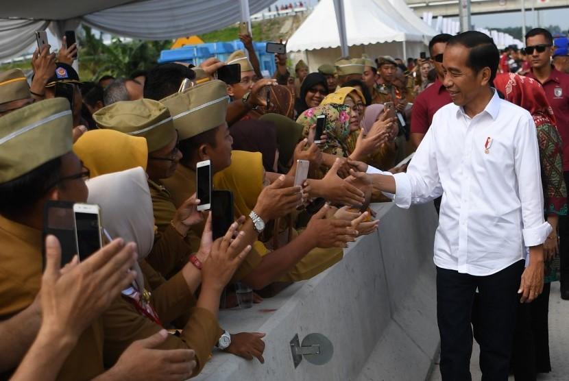 Presiden Joko Widodo menyalami aparatur sipil negara (ASN) sebelum meresmikan tol Trans Sumatera ruas Bakauheni-Terbanggi Besar di Gerbang Tol Natar, Lampung Selatan, Lampung, Jumat (8/3/2019).