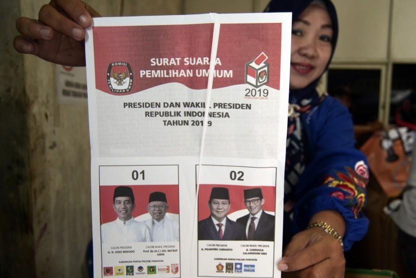 Petugas dari Komisi Pemilihan Umum (KPU) memperlihatkan surat suara Pilpres yang rusak ketika menyortir dan melipat surat suara di gudang penyimpanan logistik KPU Kota Bandar Lampung, Lampung, Jumat (8/3/2019).