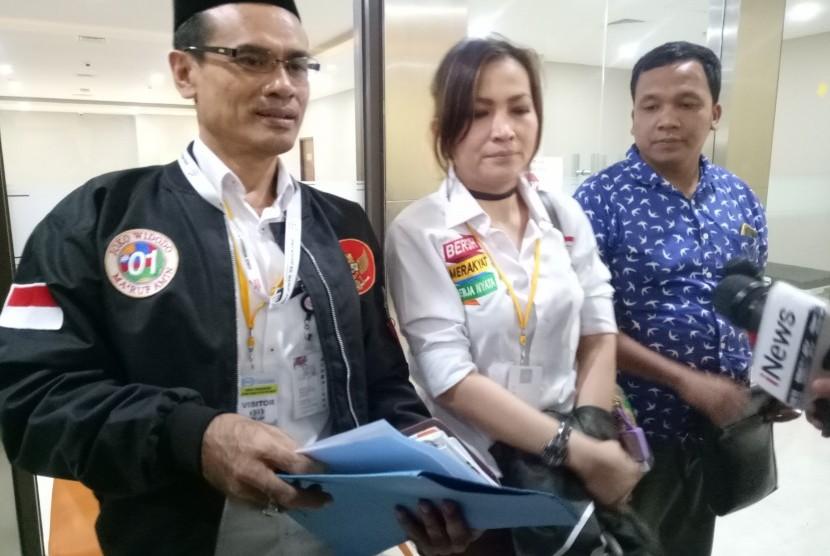 Wakil Direktur Direktorat Hukum dan Advokasi TKN, Pasang Haro Rajagukguk (pakai peci) dan Jubir Direktorat Hukum dan Advokasi TKN, Erlinda (tengah) di Gedung Siber Bareskrim Polri, Jakarta Selatan, Jumat (8/3) sore.