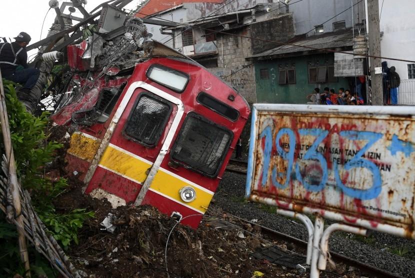 Petugas melakukan proses evakuasi KRL Commuter Line 1722 yang anjlok di pintu perlintasan Kebon Pedes, Tanah Sareal, Kota Bogor, Jawa Barat, Ahad (10/3/2019).