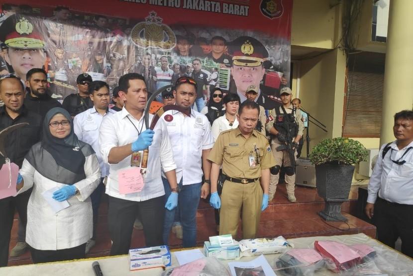 Sejumlah barang bukti yang digunakan para pelaku saat melakukan pembegalan di Jalan Daan Mogot beberapa waktu lalu, ditunjukan dalam konferensi pers di halaman Mapolres Metro Jakarta Barat, Senin (11/3) sore.