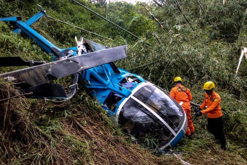 Petugas Basarnas memeriksa helikopter B-105 PK EAH milik PT Air Transport Service yang jatuh di Desa Jayaratu, Kabupaten Tasikmalaya, Jawa Barat, Sabtu (16/3/2019).