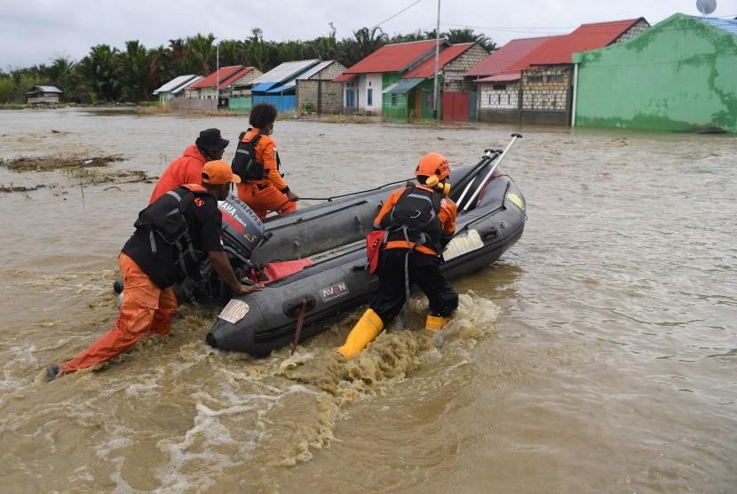 Anggota Basarnas mendorong perahu karet ketika melakukan evakuasi jenazah korban banjir bandang Sentani yang di temukan di sekitar perumahan Gajah Mada di Sentani, Jaya Pura, Papua, Selasa (19/3/2019).