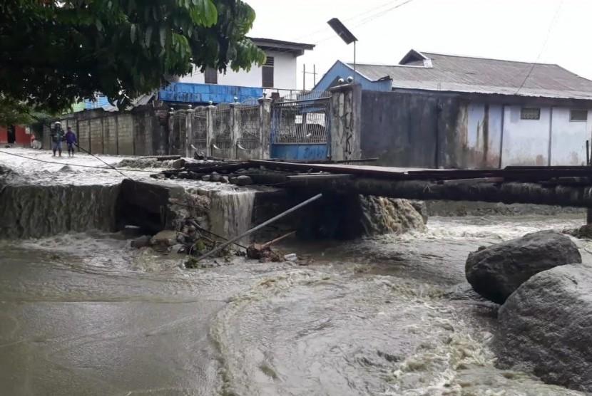 Jembatan ambrol akibat banjir bandang di Hinekombe, Sentani, Jayapura, Papua, Kamis (21/3). Warga kemudian bersama Baznas membangun jembatan darurat dengan menggunakan bahan kayu.
